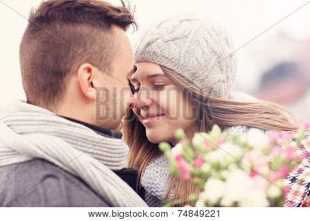 A picture of a romantic couple with flowers on an autumn walk