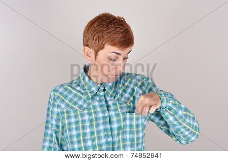 Woman looking at her empty pocket of her tartan shirt