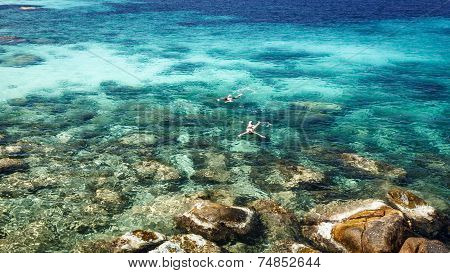 Couple Snorkelling In Crystal Clear Sea At Tropical Island
