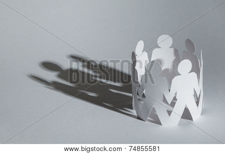 Team of paper doll people holding hands, isolated on white. Concept of friendship and support