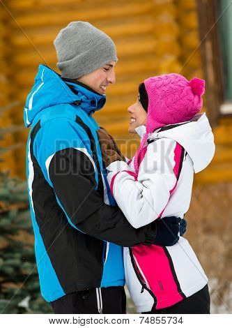 Half-length portrait of embracing couple who wears warm caps and jackets during winter holidays