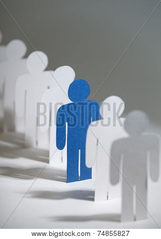 Close up of group of paper-men standing in a row. Lots of similar copies of a paper man, but a blue one stands out among them