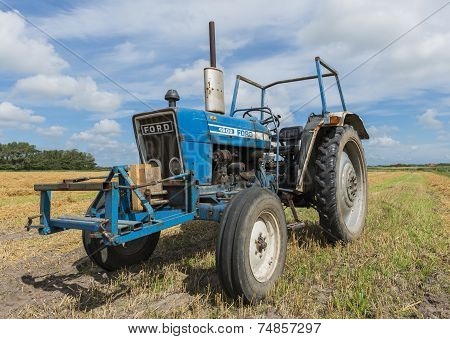 Old Blue Tractor On Grain Field