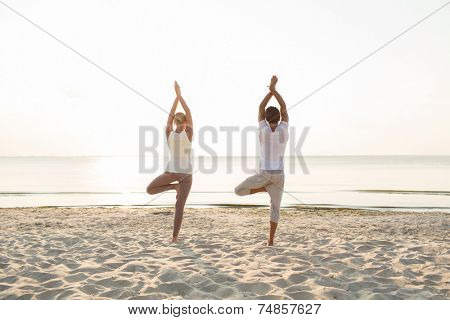 fitness, sport, people and lifestyle concept - couple making yoga exercises on sand outdoors from back