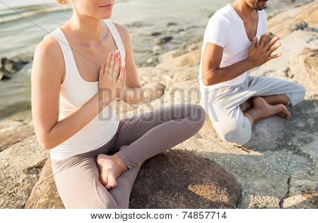 fitness, sport, people and lifestyle concept - close up of couple making yoga exercises sitting on pier outdoors
