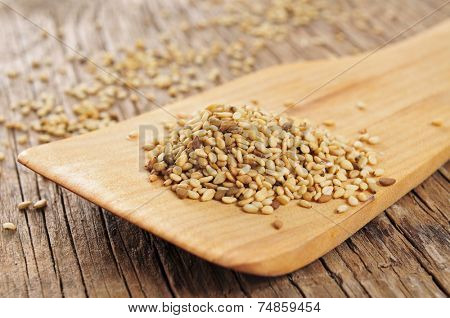 sesame seeds in a wooden spatula on a rustic wooden table