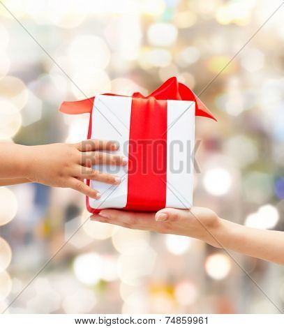 holidays, present, christmas, childhood and happiness concept - close up of child and mother hands with gift box over lights background