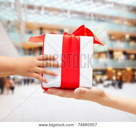holidays, present, christmas, childhood and happiness concept - close up of child and mother hands with gift box over shopping center background