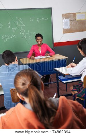 Portrait of young female teacher sitting with students in classroom