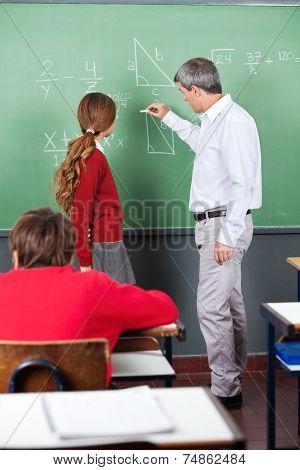 Mature male professor teaching mathematics to teenage schoolgirl in classroom