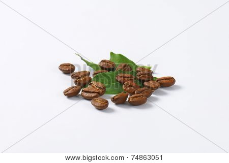 scattered coffee beans, decorated with green leaves