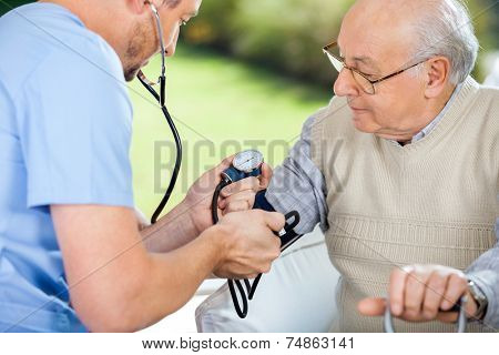 Male nurse checking blood pressure of senior man at nursing home
