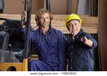 Senior carpenter gesturing while standing by colleague in workshop