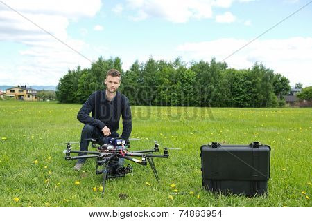Portrait of young engineer with UAV helicopter in park