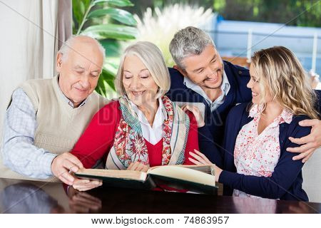Happy senior couple reading book while grandchildren looking at each other in nursing home