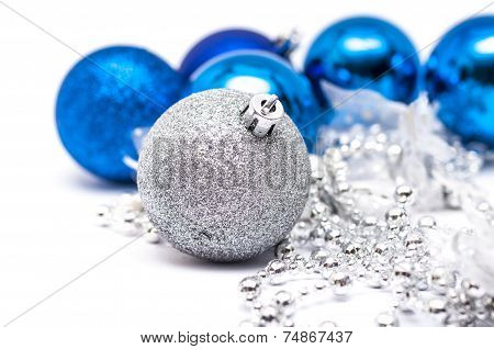 Christmas Blue  Ball In  Focus And Blue Balls In Background With Ribbons And Snow On Th Right Side