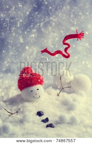 Melting snowman with scarf blowing in the wind - vintage tone effect added