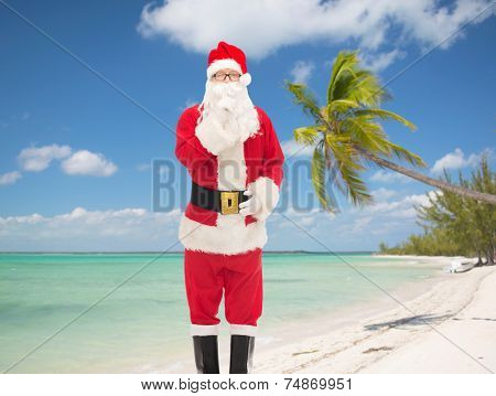 christmas, holidays, travel and people concept - man in costume of santa claus making hush gesture over tropical beach background