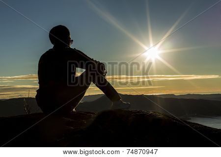Silhouette of a man sitting on a mountain looking at the sun