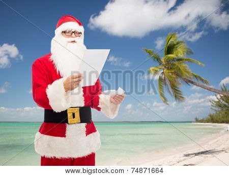 christmas, holidays, travel and people concept - man in costume of santa claus reading letter