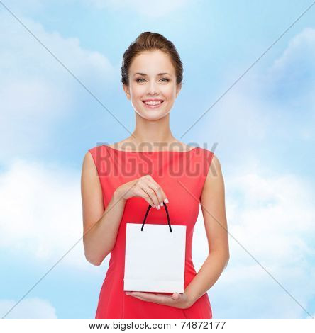 shopping, sale, christmas and holiday concept - smiling elegant woman in red dress with small shopping bag
