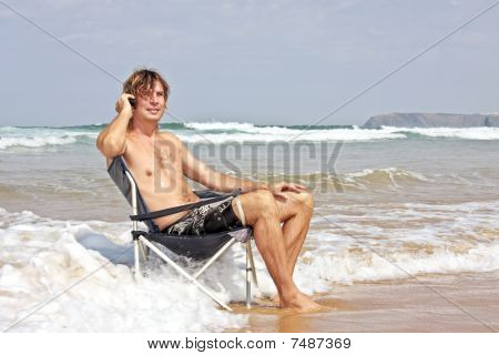 Young guy making a phone call sitting in the water from the ocean