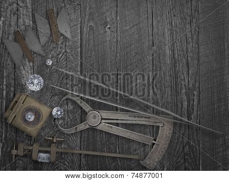 faded colors vintage jewelers tools and diamonds over wooden bench, space for text