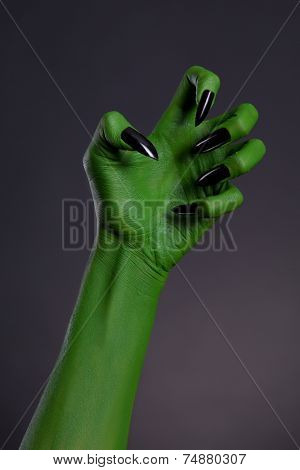 Green witch hand with sharp black nails, real body-art, Halloween theme