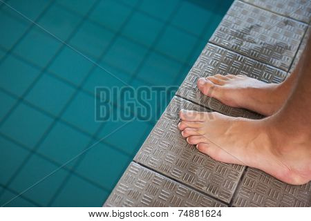 Close up low section of barefeet by the pool at leisure center