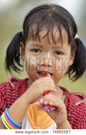 MAE SOT, THAILAND, NOVEMBER 12, 2012 : Portrait of unidentified Burmese little girl eating a liquid sugar candy near Mae Sot, North Thailand.