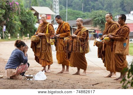 PHANG MAPHA, THAILAND, NOVEMBER 19, 2012: women giving daily food at the Buddhist monks during early morning traditional alms in the village of Phang Mapha, Thailand
