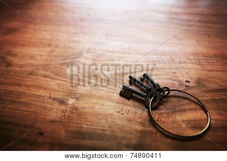 Old keys with an brass ring, on old rustic wood surface. Shallow depth of field.