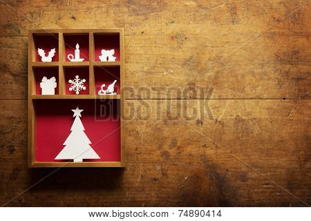 Christmas decoration on a rustic or  grungy wooden wall, with plenty of copy space. Paper Christmas decoration (hand cut) in a wooden display tray.