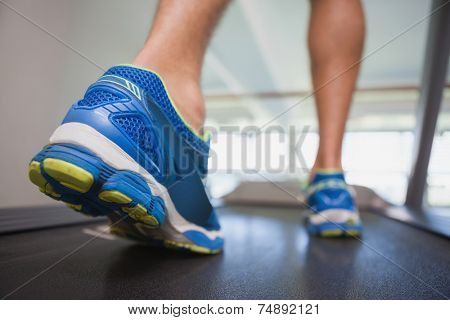 Rear view low section of a man running on treadmill in the gym
