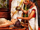 stock photo of sari  - Young woman having oil Ayurveda spa treatment - JPG