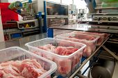 foto of slaughterhouse  - Workers taking the lumps of meat in a container - JPG