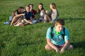 stock photo of peer-pressure  - Depressed male teenage student sitting alone outdoors - JPG