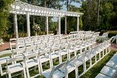 stock photo of lawn chair  - White chairs lined up before an outdoor summer wedding - JPG