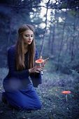 stock photo of witch  - beautiful witch holding a mushroom in dark forest - JPG