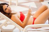 foto of pov  - Pretty young Hispanic woman relaxing by a pool and texting with her mobile phone - JPG