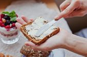 picture of margarine  - woman hand rubs butter on piece of rye bread - JPG