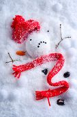 stock photo of bobble head  - Melted snowman with knitted hat and scarf - JPG