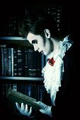 picture of dracula  - Handsome vampire nobleman studying ancient books in the library - JPG