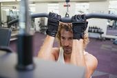 stock photo of lats  - Close up of a handsome young man exercising on a lat machine in gym - JPG