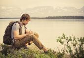 stock photo of writing  - Young Man Traveler with backpack reading book and writing notes outdoor mountains on background Summer vacations and Lifestyle concept - JPG