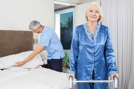 stock photo of zimmer frame  - Portrait of senior woman standing with walking frame while caretaker making her bed at nursing home - JPG
