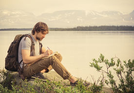 pic of boy scout  - Young Man Traveler with backpack reading book and writing notes outdoor mountains on background Summer vacations and Lifestyle concept - JPG