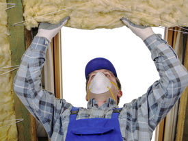 stock photo of thermal  - Worker thermally insulating a house attic using mineral wool - JPG