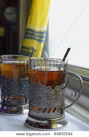 Two cups of tea on a table in a train compartment