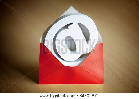 E-mail at symbol inside a red envelope on a desk